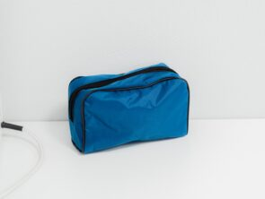 Blue cloth medical bag, cosmetic bag with black zipper stands on white table. First aid kit in light interior